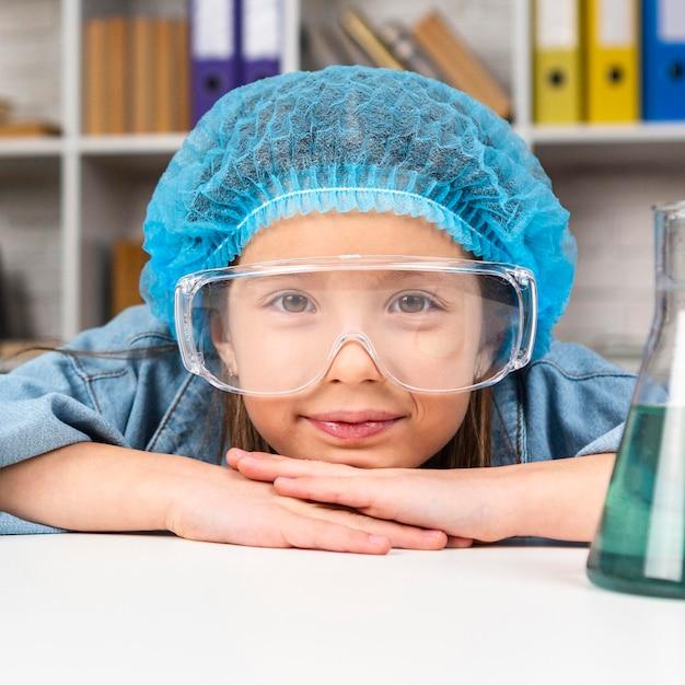 과학 실험을 위해 머리 그물과 안전 안경을 착용하는 동안 포즈를 취하는 소녀 무료 사진