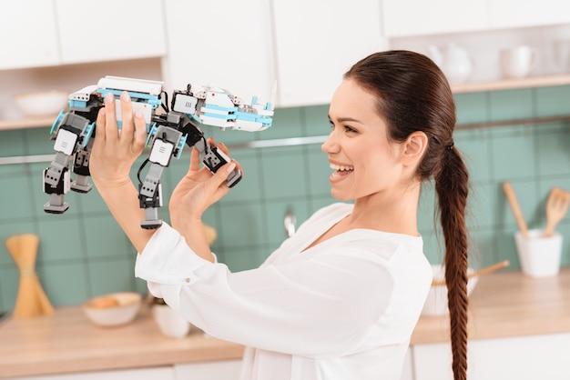 モダンな美しいキッチンでサイのロボットとポーズの女の子。 Premium写真