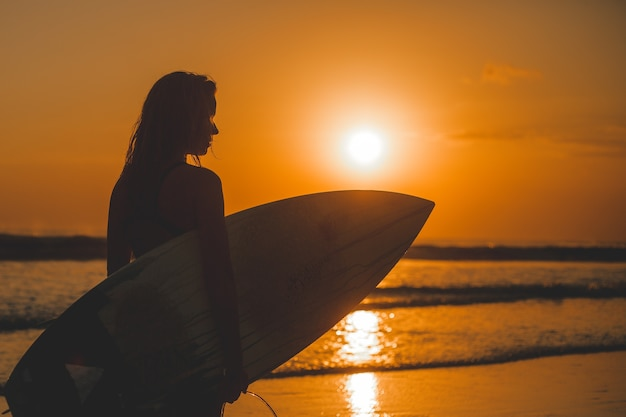 Girl posing with a board at sunset Free Photo