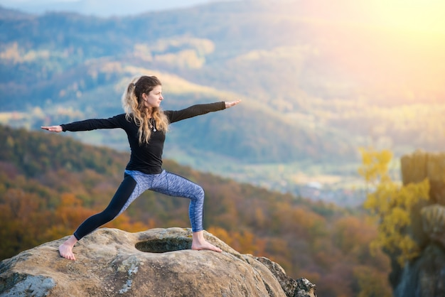 Girl practicing yoga, doing asana on the top of the mountain Premium Photo