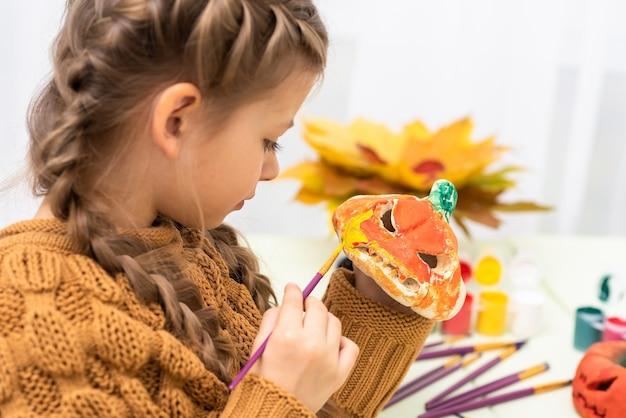 Девушка готовит тыкву на праздник хэллоуина. Premium Фотографии
