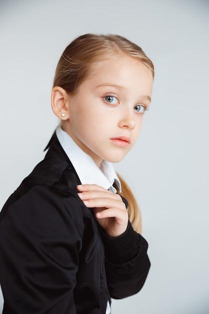 긴 여름 방학 후 학교를 준비하는 소녀. 학교로 돌아가다. 흰 벽에 학교의 제복을 입은 작은 여성 백인 모델 포즈. 어린 시절, 교육, 휴일 개념. 무료 사진