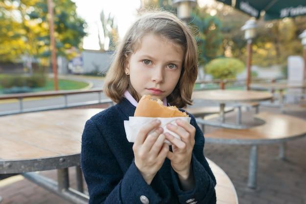 여자 초등 학생 야외 카페에서 햄버거, 샌드위치를 먹는다 프리미엄 사진