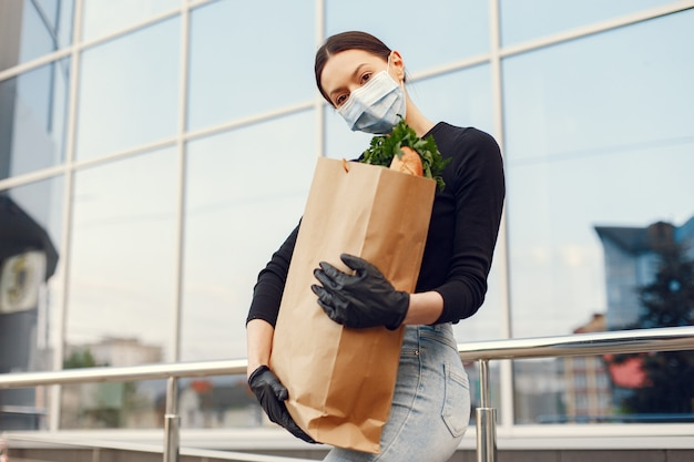Girl in protective mask holds package with products Free Photo