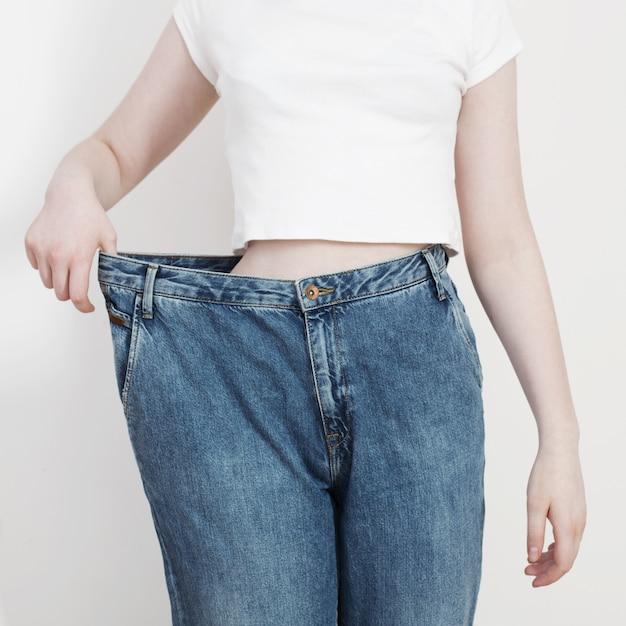 彼女の大きなジーンズを引っ張って減量を示す女の子 Premium写真