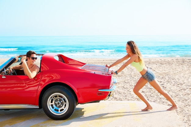 Girl pushing a broken car on the beach funny guy Premium Photo