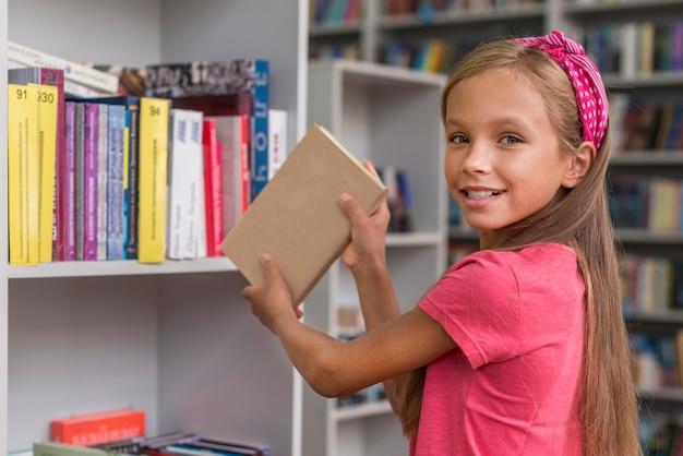 Ragazza che rimette un libro sullo scaffale Foto Gratuite