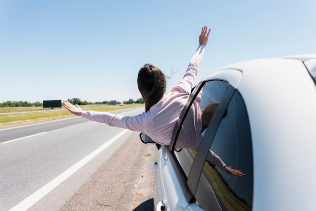 Girl putting her head out of the window car Premium Photo