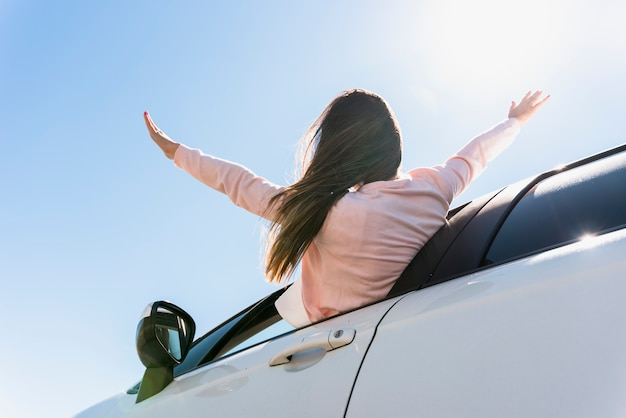 Girl putting her head out of the window car Free Photo