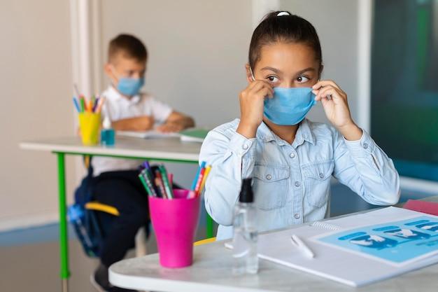 Ragazza che indossa la sua mascherina medica in classe Foto Gratuite