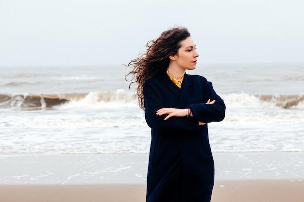 Girl rain sea wind winter portrait woman smile spring coat long hair curly mood shore snow beach Premium Photo