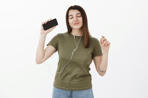 Ragazza che raggiunge il nirvana e le emozioni positive, ha vibrazioni positive dal suono fantastico degli auricolari, ascolta musica che balla sensualmente con gli occhi chiusi e un sorriso felice, alzando la mano con lo smartphone Foto Gratuite