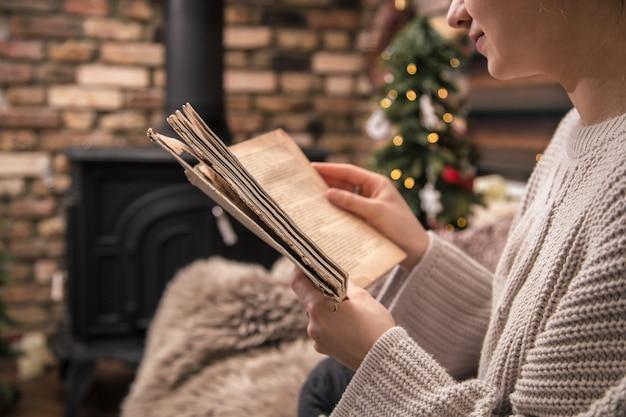Девушка читает книгу в уютной домашней обстановке у камина, крупный план Бесплатные Фотографии