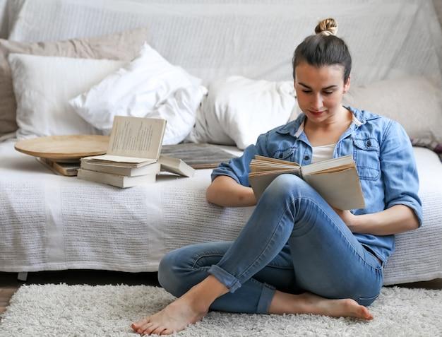 Девушка читает книгу в уютной комнате Бесплатные Фотографии