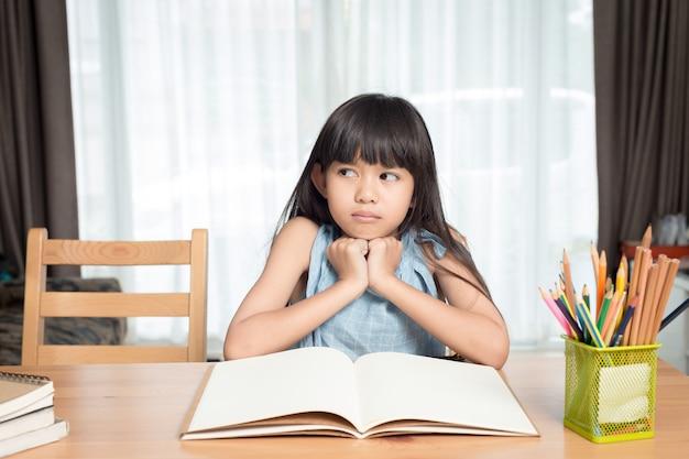 家のテーブルで本を読んでいる女の子 Premium写真