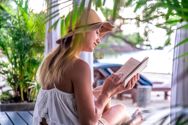 Girl reading a book on the beach Free Photo