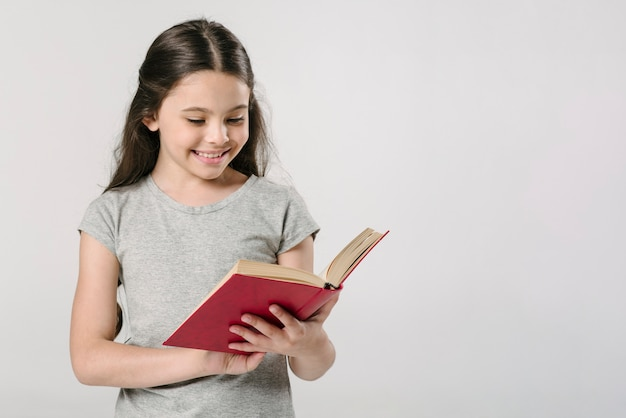 Girl reading book in studio and smiling Free Photo