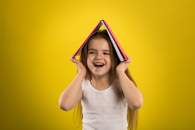 Girl reading a book in a pink cover Premium Photo