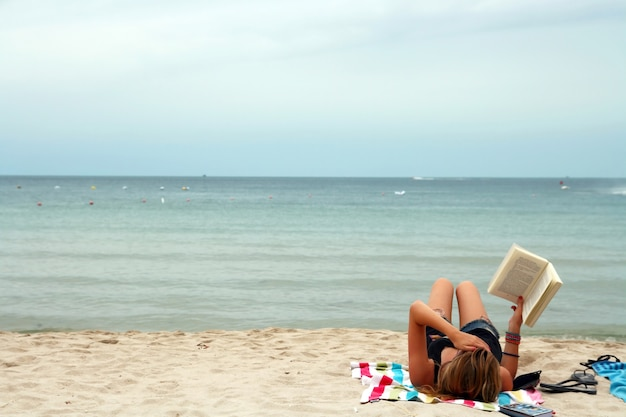 Girl reading book in relax mood on the tropical beach, samui thailand Premium Photo