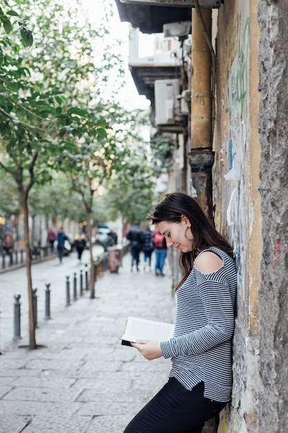 Girl reading a book in the street Free Photo