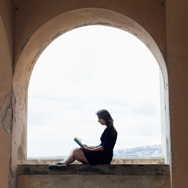 Girl reading a book on a window Free Photo