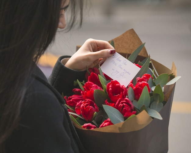 Girl reading a note put into a bouquet of red tulips Free Photo