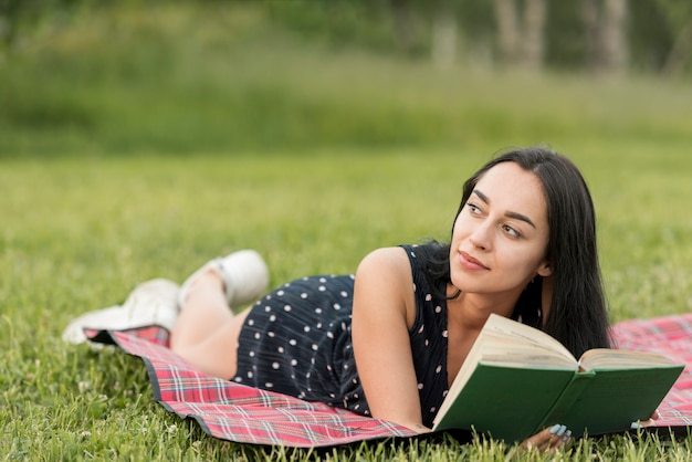 Girl reading on a picnic blanket Free Photo