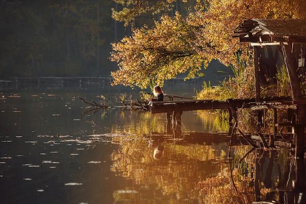 女の子は川沿いの秋に本を読みます。孤独な若い女性は木製の橋で本を読みます Premium写真