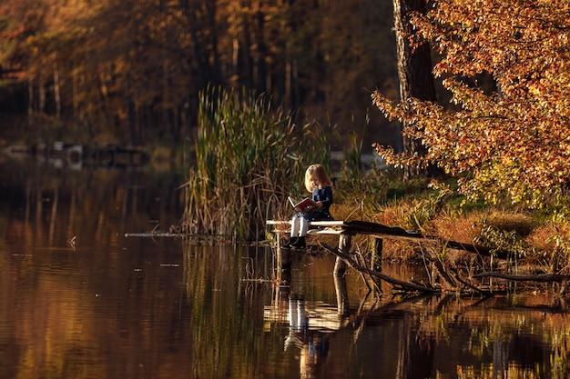 女の子は川沿いの秋に本を読みます。 Premium写真