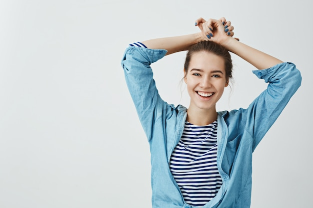 Girl relaxes after spending day in college. studio shot of good-looking emotive student holding hands on hair while smiling broadly and being carefree, expressing positive emotions over gray wall Free Photo