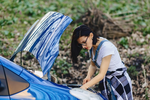 Girl repairs car with an open hood on road Premium Photo
