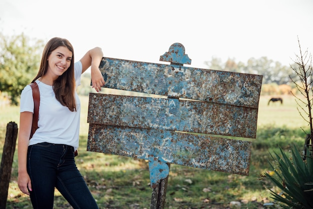 Girl resting on an old metal street sign Free Photo
