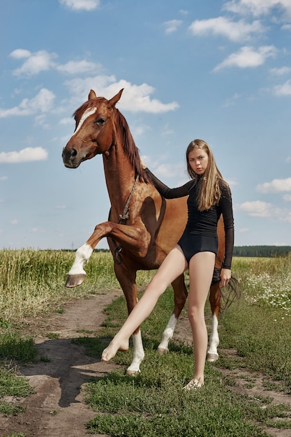 Girl rider stands next to the horse in the field Premium Photo