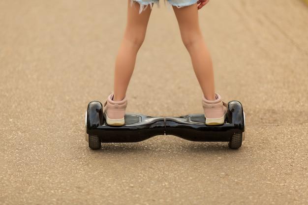 Девушка катается на гироскутере летом по площади Premium Фотографии