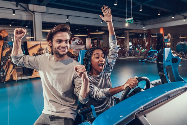 Girl riding car in arcade. guy is helping. girl is winning. Premium Photo