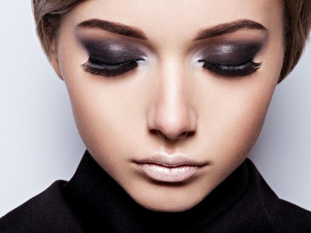 Primo piano del viso della ragazza con lunghe ciglia nere. trucco di moda Foto Gratuite