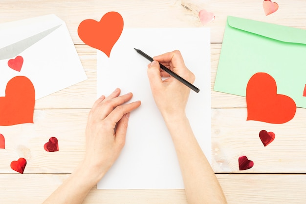 Рука девушки пишет любовное письмо. день святого валентина. открытка ручной работы с красным сердцем в виде фигуры. 14 февраля - праздник. вид сверху Premium Фотографии