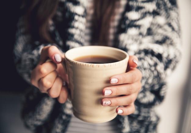 一杯のコーヒーを保持している女の子の手と Premium写真