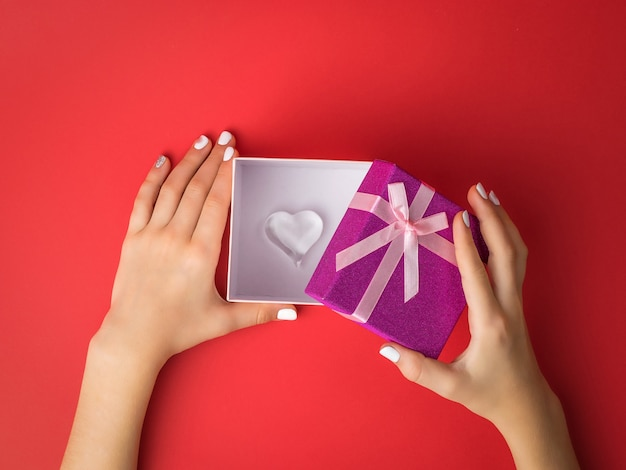 The girl's hands open a gift box with a glass heart inside. surprise in the hands of a girl. Premium Photo