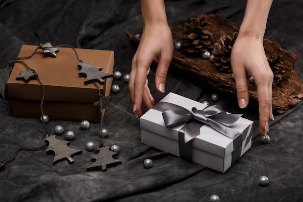 Руки девушки положить подарочной коробке на стол. новогоднее украшение фон. Бесплатные Фотографии