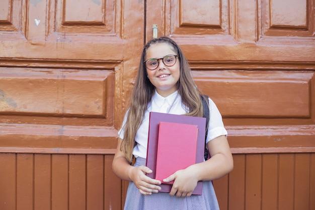 Girl in school uniform in glasses holding books and smiling Free Photo