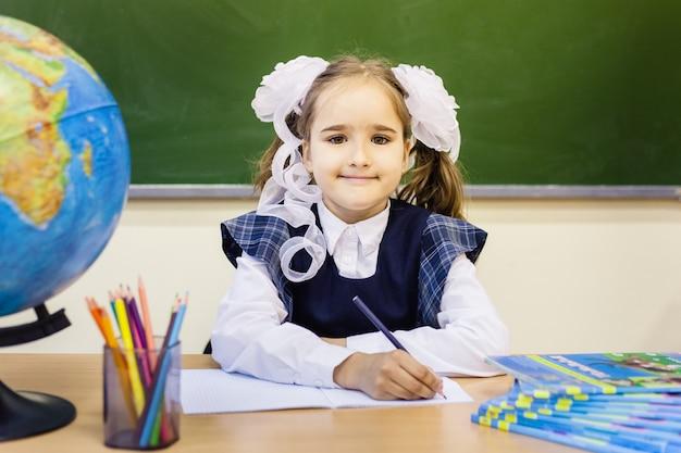 Girl schoolgirl and school. the girl wears a school uniform at school. training Premium Photo