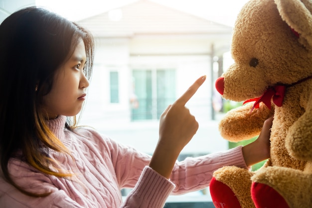 The girl scolding teddy bear in the bedroom of her home Free Photo
