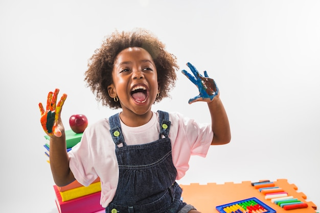 Girl screaming with hands in paint in studio Premium Photo