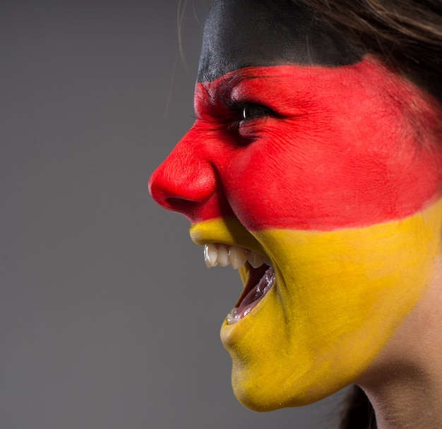 Girl screaming with a painted flag on her face. Premium Photo
