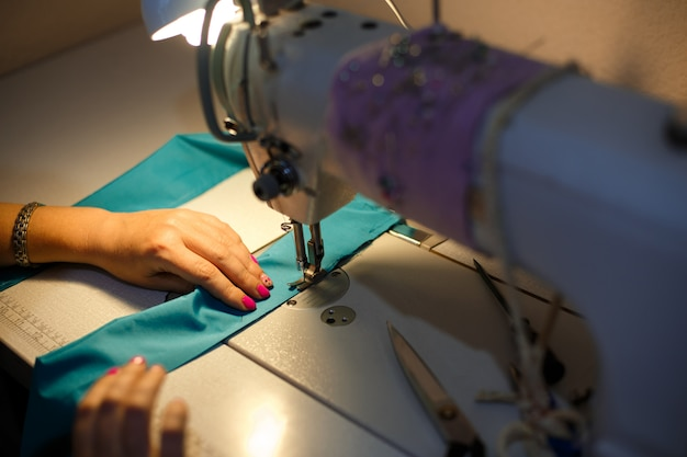 Girl seamstress in the light of a desk lamp stitching a blue cloth on a sewing machine Premium Photo