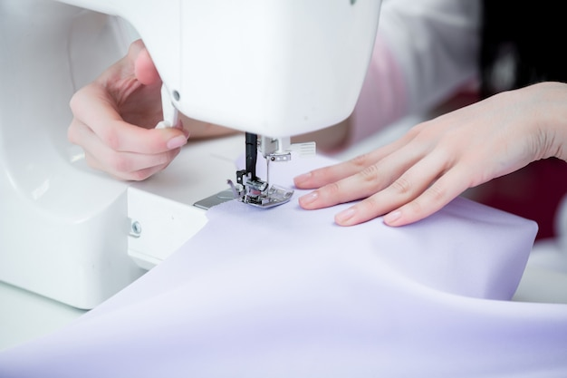 Girl seamstress sew on the sewing machine Premium Photo