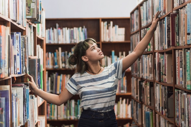 Girl searching bookshelf Free Photo