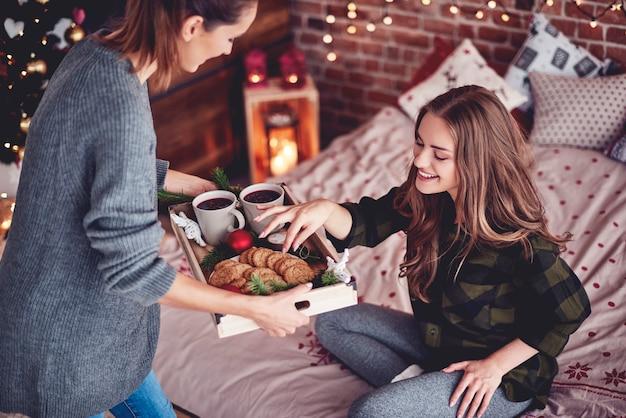 彼女の友人とクッキーとホットワインを共有する女の子 無料写真