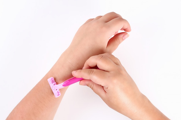 Girl shaves the hair on his hand with pink razor Premium Photo